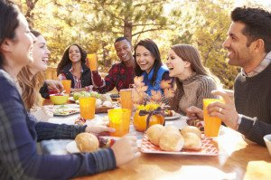 le-groupe-d-amis-heureux-mangent-et-rient-d-une-table-à-un-barbecue-78931917